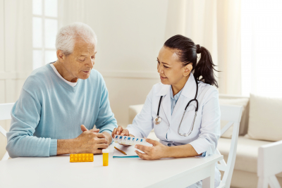 Nice professional female doctor holding a box of pills and giving them to her elderly patient